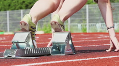 Close up of a female legs in a running spikes on a starting blocks - slow motion Stock Footage