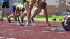 A start of young athletes on a start line on a stadium - slow motion, feet level Stock Footage