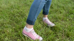 Close up of Girl in jeans and sneakers dancing on the green grass in the park Stock Footage