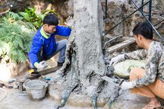 Workers are grout cement on the fake tree trunk Stock Photos