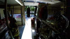Firemen climbing into fire trucks in garage Stock Footage