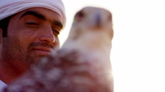 Trained falcon tethered to male owner wearing traditional Arabic dress Stock Footage