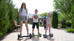Children ride on a Segway motorized scooters hoverboard in the park Stock Footage