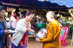 People put food on buddhist monk alms bowl - stock photo