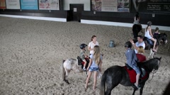 Children are trained to ride horses in the aviary on the sand - stock footage