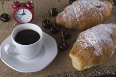 Alarm clock and breakfast with cherry, coffee , croissant. - stock photo