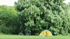 mother with little daughter playing Tent and Cargo bike in the picnic nature  - stock footage