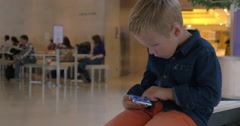 Kid with mobile phone in shopping mall Stock Footage
