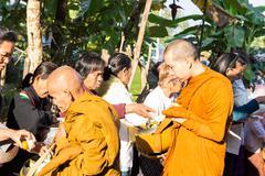 People put food on buddhist monk alms bowl Stock Photos