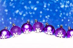Christmas purple balls in snow on blue glitter background Stock Photos