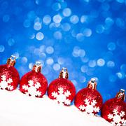 Christmas red balls in snow on blue glitter background Stock Photos