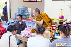 Buddhist monk is blessing people - stock photo