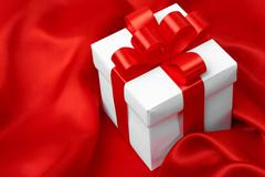 Gift on red satin background Stock Photos