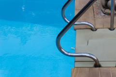 Metal handrail at poolside Stock Photos
