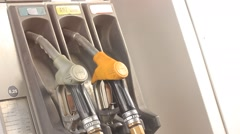 Fuel nozzle with hose at gas station pump - stock footage