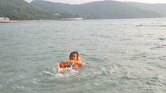 Funny asian girl swimming in sea, - stock footage