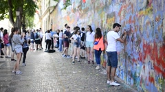 A Young  Tourist is Signing on the Lennon's Wall in Prague Stock Footage
