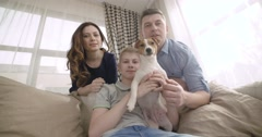 Happy family with cute dog talking to relatives using video chat on laptop at Stock Footage