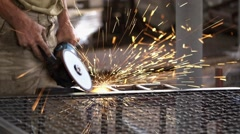 Worker with Angle Grinder does Metalworking in Industrial Environment. Stock Footage