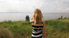 blonde is walking on a field in sunny weather,back view,sea on background - stock footage