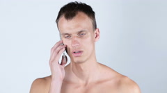 Young shirtless man talking on his mobile phone Stock Footage