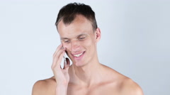Portrait of cheerful handsome shirtless man talking on the phone Stock Footage