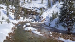 Aerial view of waterfall and snow covered mountain Stock Footage