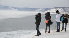 A group of young tourists visit winter lake in mountains and take pictures of - stock footage