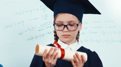 Close up portrait little student girl 7-8 years graduate in the mantle Stock Footage