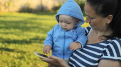 Baby boy hold by mother in the park. Mum calling at the phone Stock Footage