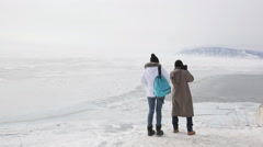 Couple travelers visiting lake with mountains in winter and take pictures - stock footage