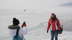 Two women tourists are photographed on a background of icy lakes and mountains Stock Footage