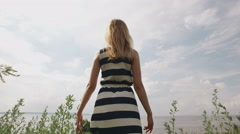 Blonde in striped dress is standing on a field, looking on a sea, lifting hands Stock Footage