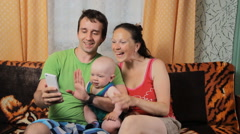 Mom, little baby and dad are doing video communication on the phone. Family Stock Footage
