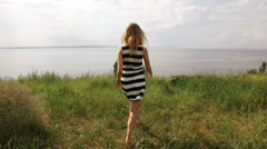 Young shapely blonde is walking on a field, looking on a sea in summertime Stock Footage
