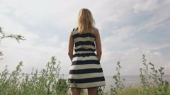 Blonde dressed in striped dress is standing on a field near sea, lifting hands Stock Footage
