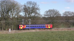 Colourful commuter train travelling through countryside panning Stock Footage