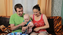 Mom, little baby and dad are touch smartwatch. Family sitting at home on the Stock Footage