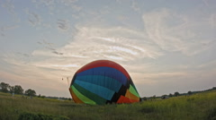 Hot air balloon burner firing and inflates the envelope, wide angle - stock footage