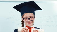 Close up portrait little student girl graduate in the mantle showing diploma - stock footage
