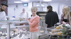 4K Adult mother & daughter shopping at cheese counter in grocery store Stock Footage