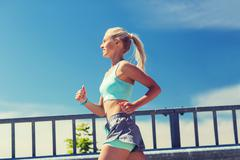 smiling young woman running outdoors - stock photo