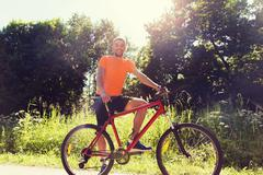 happy young man riding bicycle outdoors - stock photo