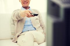 close up of happy senior woman watching tv at home - stock photo