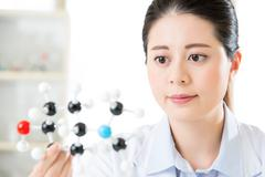 Asian female scientist looking at molecular model doing the science research Kuvituskuvat