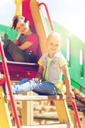 happy kids or children on playground slide - stock photo