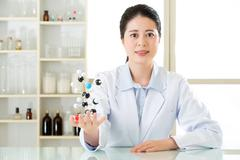 Asian female scientist teacher point at molecular model explain Scientific wo Stock Photos