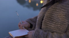 Sad, upset woman near the river while vents her grief by writing the diary - stock footage