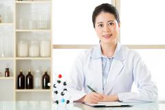 Happy asian female scientist with holding pen on clipboard in the laboratory Stock Photos