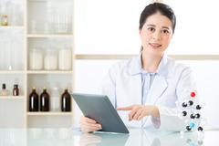 Asian female chemist use notepad to research for future Chemical formula Stock Photos